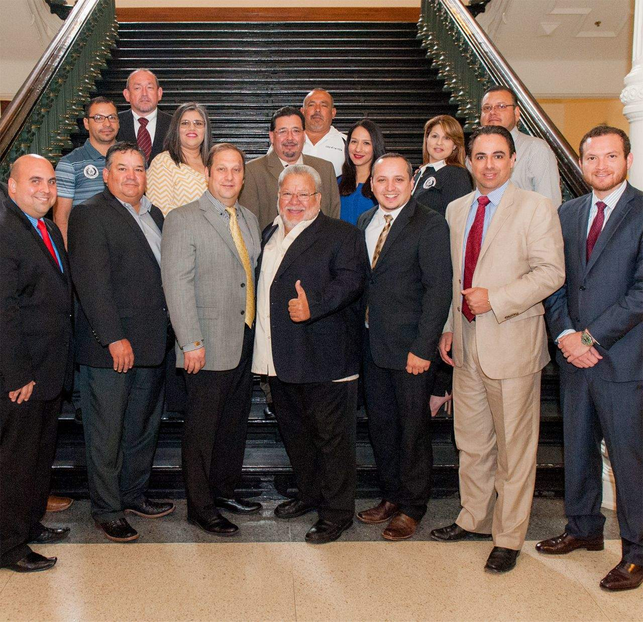 "Featured, front row, from left: Rep. Armando ""Mando"" Martínez, D-Weslaco; Elsa Mayor Al Pérez; Edcouch-Elsa ISD School Board Trustee Víctor ""Hugo"" De la Cruz; Edcouch Mayor Pro Tem Eddy González; Edcouch Mayor Robert Schmalzried; Rep. Terry Canales, D-Edinburg; and Rep. Óscar Longoria, Jr., D-La Joya. Middle row, from left: La Villa City Manager Arnie Amaro; Edcouch Alderwoman Verónica Solis; Edcouch City Manager Noé Cavazos; Edcouch Alderwoman Rina Castillo; La Villa Commissioner Rosie Pérez; and Edcouch Alderman Danny Guzmán. Back row, from left: Elsa City Manager Juan Zuniga; and La Villa Commissioner Mario López. The lawmakers and constituents posed for this portrait inside the Texas Capitol following House passage on Friday, May 8, of House Bill 382, which proposed creating a South Texas College branch campus in the Delta Region of Hidalgo County. Photograph By HOUSE PHOTOGRAPHY"